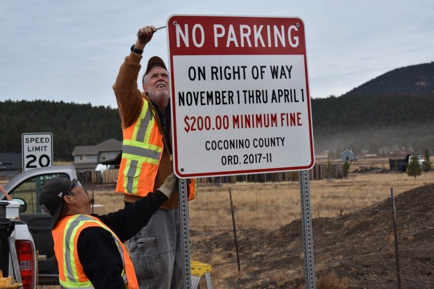 County employee posting sign about parking ordinance